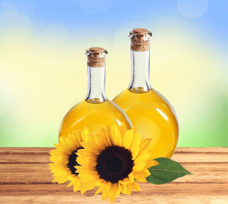 Oliwi w butelkach i słonecznikach na drewnianym stole nad natury backgr obrazy stock