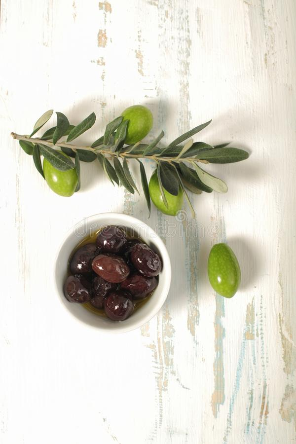 Oliwki w porcelana pucharze potomstwo oliwnej gałązce na drewnianym backgr i zdjęcia stock