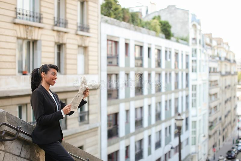 Oliwkowego dziennikarza czytelniczy gazetowy pobliski wysoki budynek zdjęcie royalty free