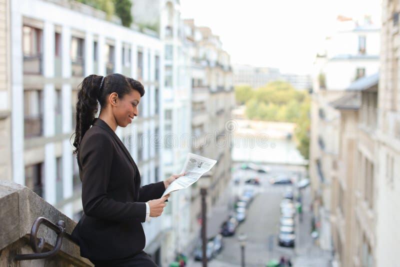Oliwkowego dziennikarza czytelniczy gazetowy pobliski wysoki budynek obrazy royalty free