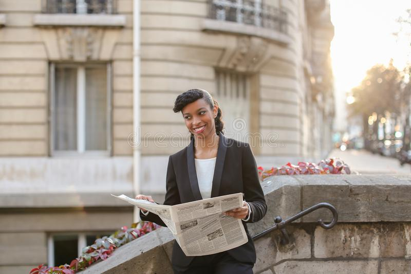Oliwkowego dziennikarza czytelniczy gazetowy pobliski wysoki budynek zdjęcie stock