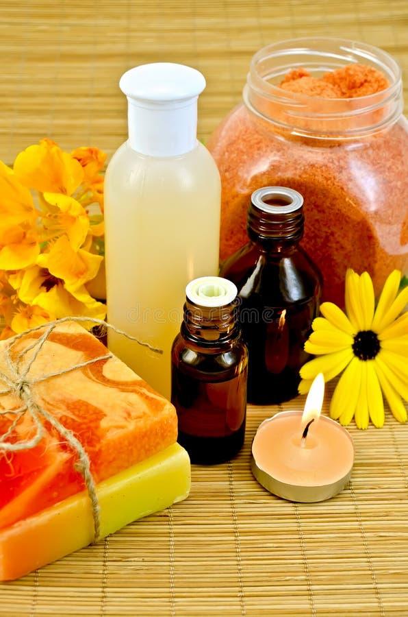 Olja och lotion med blommor och stearinljuset arkivbilder