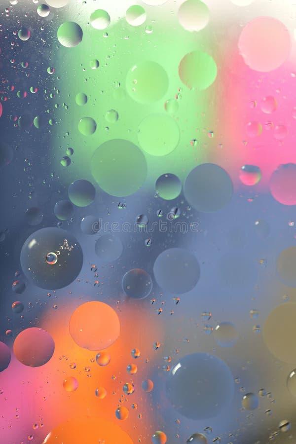 Olja tappar i vatten p? en kul?r bakgrund Ljus bakgrund med blåa, rosa, orange och gröna cirklar av olika format stock illustrationer