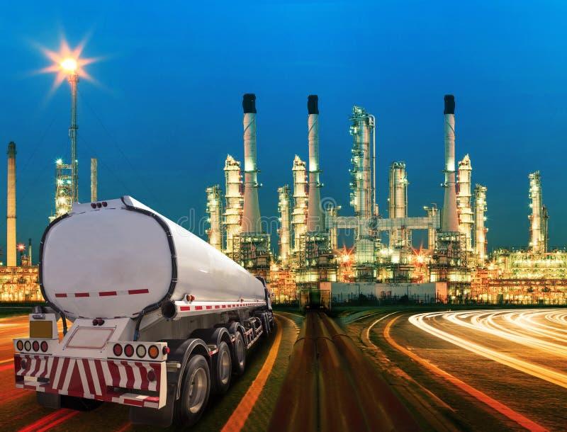Oljabehållarelastbil och härlig belysning av oljeraffinaderiet arkivbild