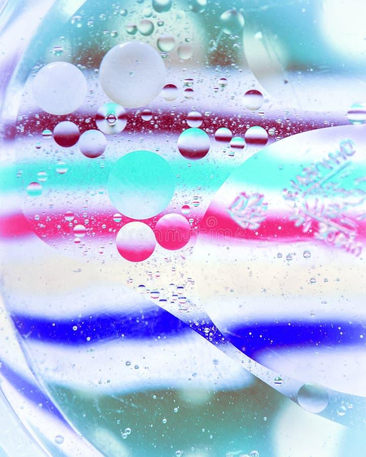 Oljadroppar på en vattenyttersida med färgglad bakgrund royaltyfri fotografi