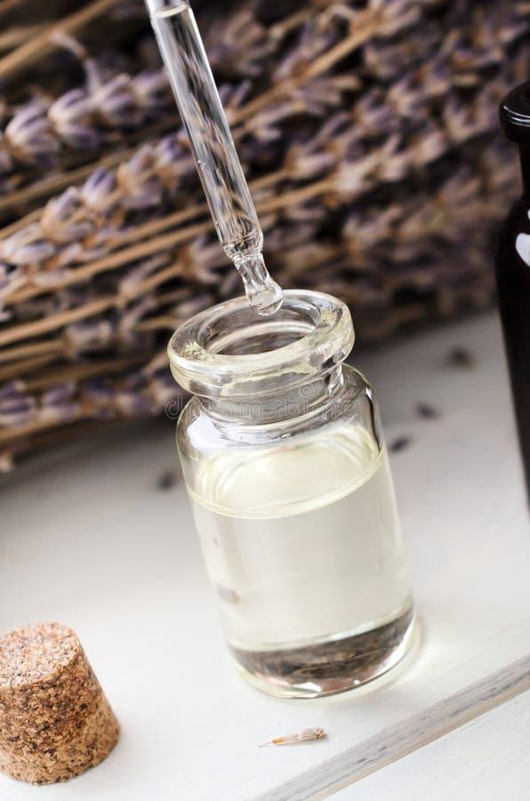 Oljastekflott in i exponeringsglaslilla medicinflaskan från pipetten med lavendel Herb Flowers i bakgrund arkivbild