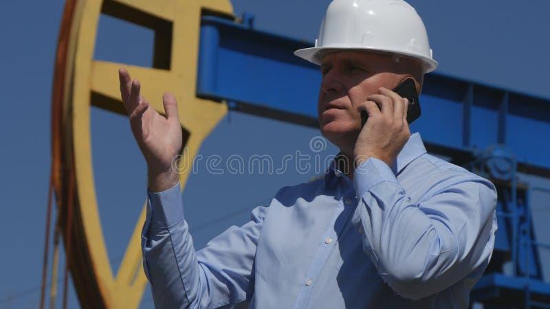 Oljatekniker Working, i utdragning av oljeindustrisamtal till mobilt göra en gest royaltyfria foton