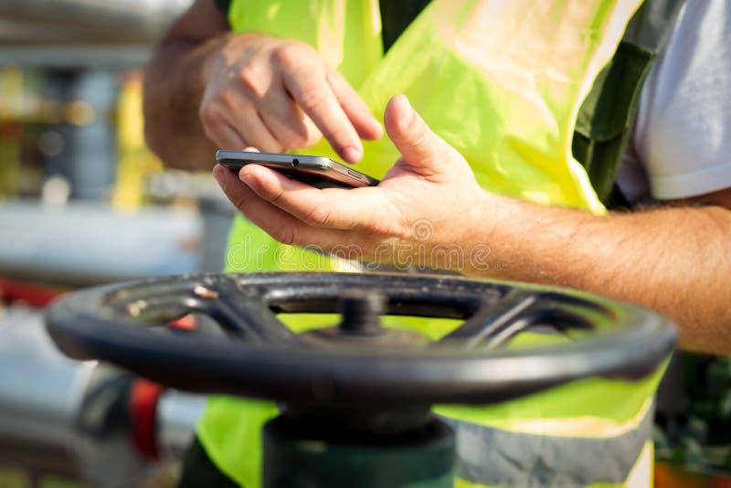 Olje- arbetare som använder den smarta telefonen royaltyfri foto
