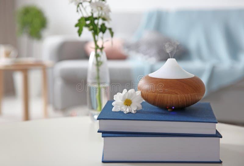 Olje- diffusor för arom på bunt av böcker royaltyfri foto
