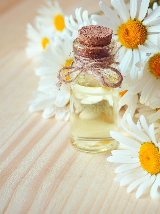 Olje- flaska för kamomill med blommor på träbakgrund arkivfoton