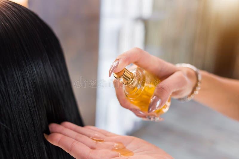 Olje- hårbehandling för kvinna Spa skönhetsalong Håromsorg i modern brunnsortsalong frisörkvinnan applicerar en maskering eller e royaltyfria foton