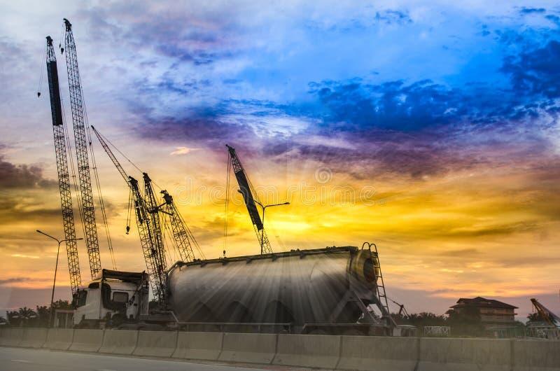 Olje- lastbil och hög kran i solnedgånghimmel royaltyfri bild