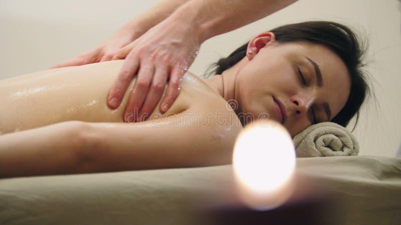 Olje- massage - händer för man` s på baksidan av flickan för svart hår royaltyfri bild