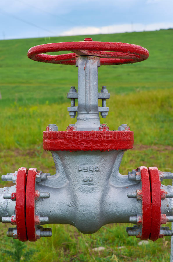 Olje- rörledning för ventil till en närbild på en bakgrund av grönt gräs och blå himmel arkivfoto