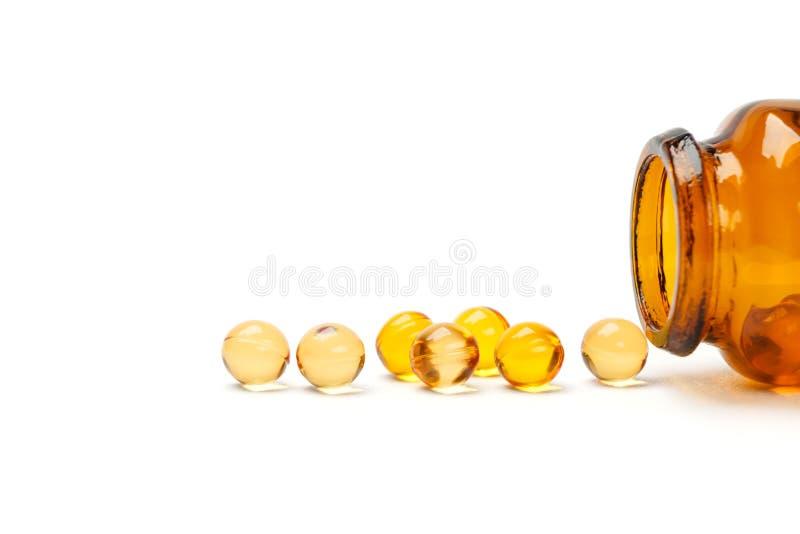 Olje- vitaminkapsel med flaskan royaltyfri bild