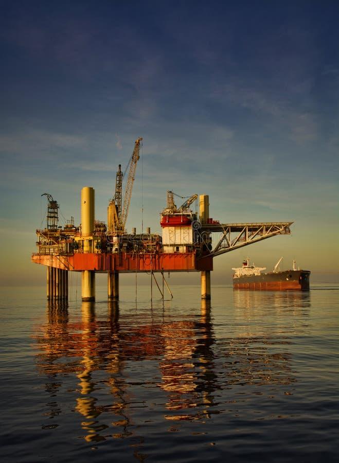 Oljeplattformplattform under solnedgång arkivfoto