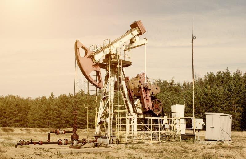 Oljeproduktion den olje- brunnen står på fältet bland skogen, blå himmel, extraktion av oljor som är industriell, maskinen som to royaltyfri foto