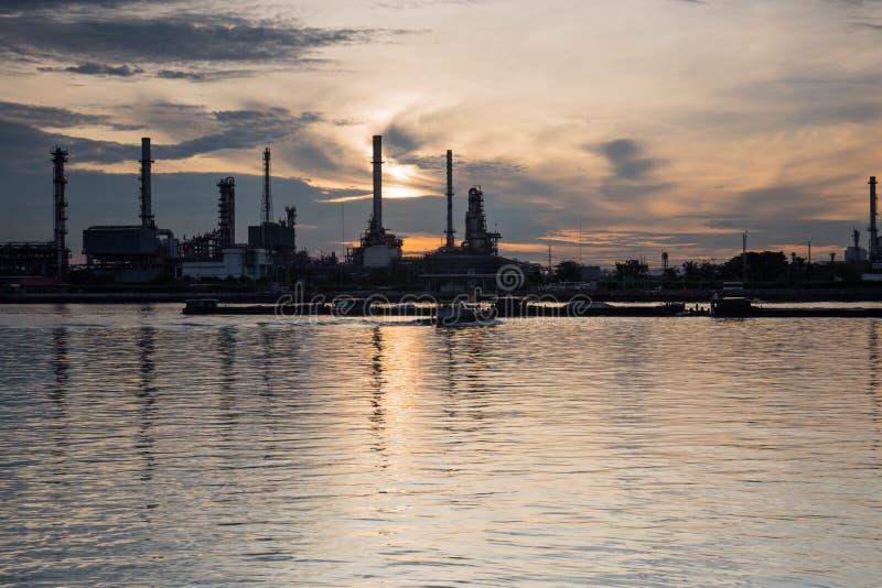 Oljeraffinaderiflodstrand- och vattenreflexion arkivbild