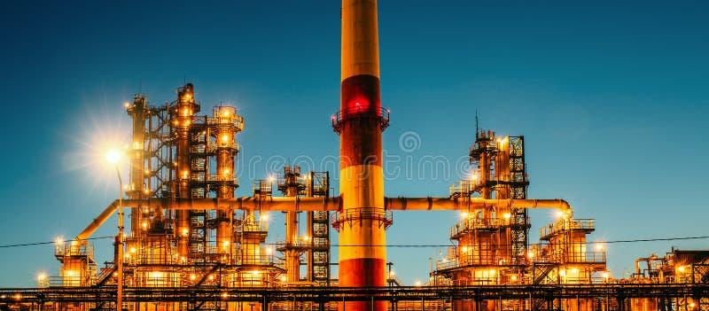 Oljeraffinaderiindustrianläggning eller fabrik på solnedgången, lagringsspritfabrikbehållare och stålrörledningen, moderna petrok arkivbild