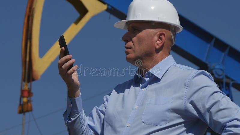 Oljor iscensätter Working, i utdragning av oljeindustri som använder mobiltelefonen royaltyfri foto