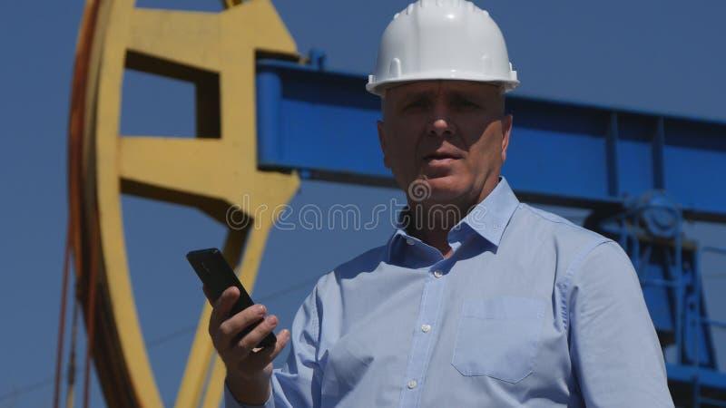 Oljor iscensätter Working, i utdragning av oljeindustri som talar med mobiltelefonen royaltyfria bilder