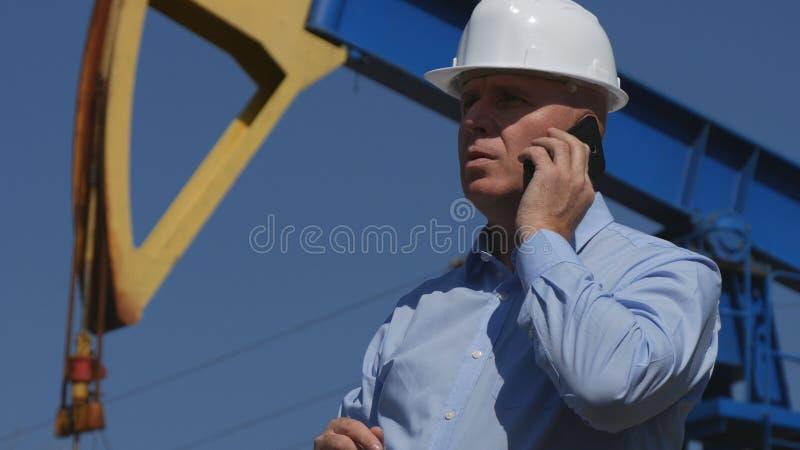 Oljor iscensätter Working, i utdragning av oljeindustri som talar till mobiltelefonen arkivbilder