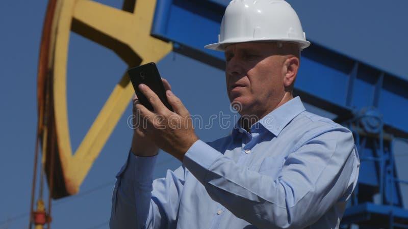 Oljor iscensätter Working, i utdragning av oljeindustritext genom att använda mobilen royaltyfria foton