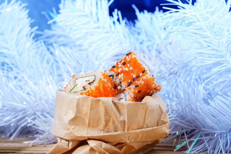 Olla dei sushi durante un nuovo anno insolito che imballa, contro un albero di natale bianco immagine stock