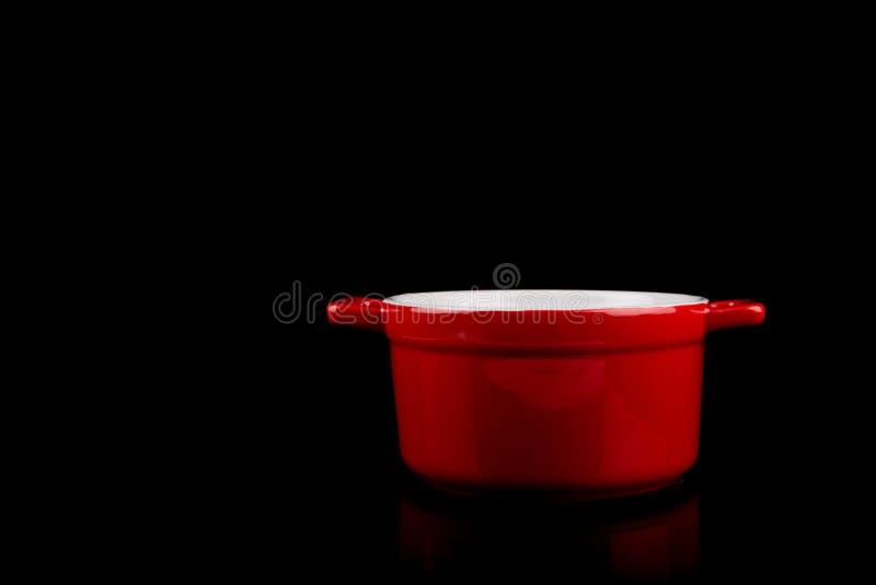 Olla, olla roja aislada en el fondo negro con reflexiones, espacio de la copia fotografía de archivo libre de regalías