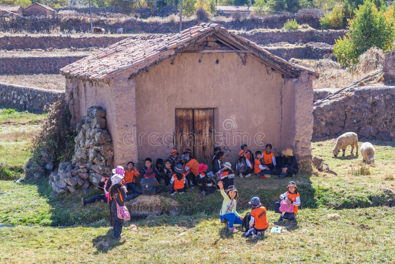 Ollantaytambo,秘鲁-大约2015年6月:传统秘鲁衣裳的孩子在库斯科,秘鲁附近等待schoold公共汽车 免版税库存照片