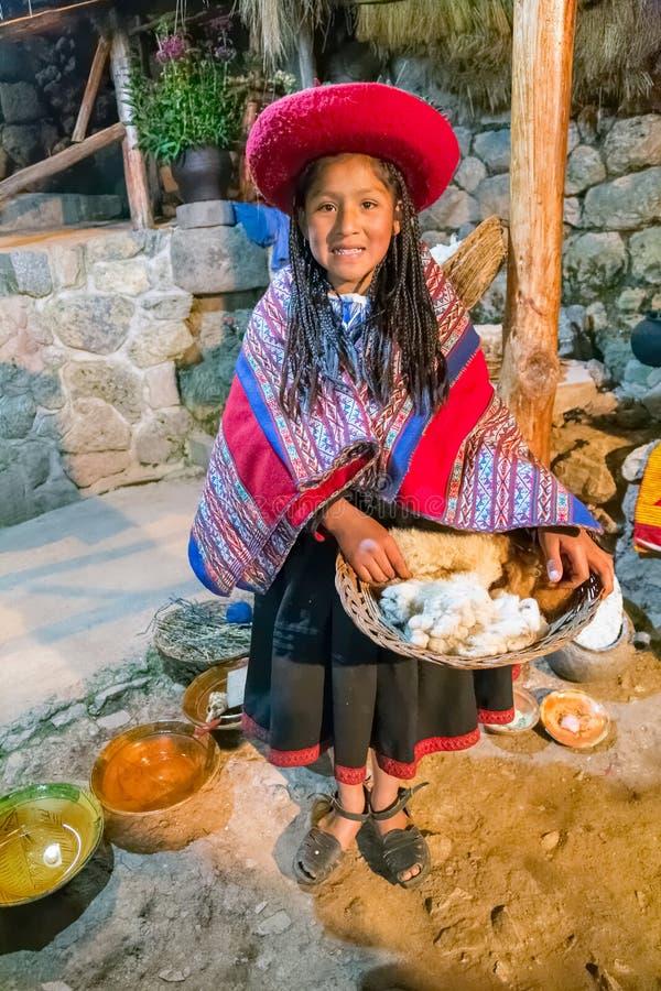 Ollantaytambo,秘鲁-大约2015年6月:传统秘鲁衣裳的女孩在库斯科附近拿着与羊魄和骆马羊毛的一个篮子, 免版税库存照片