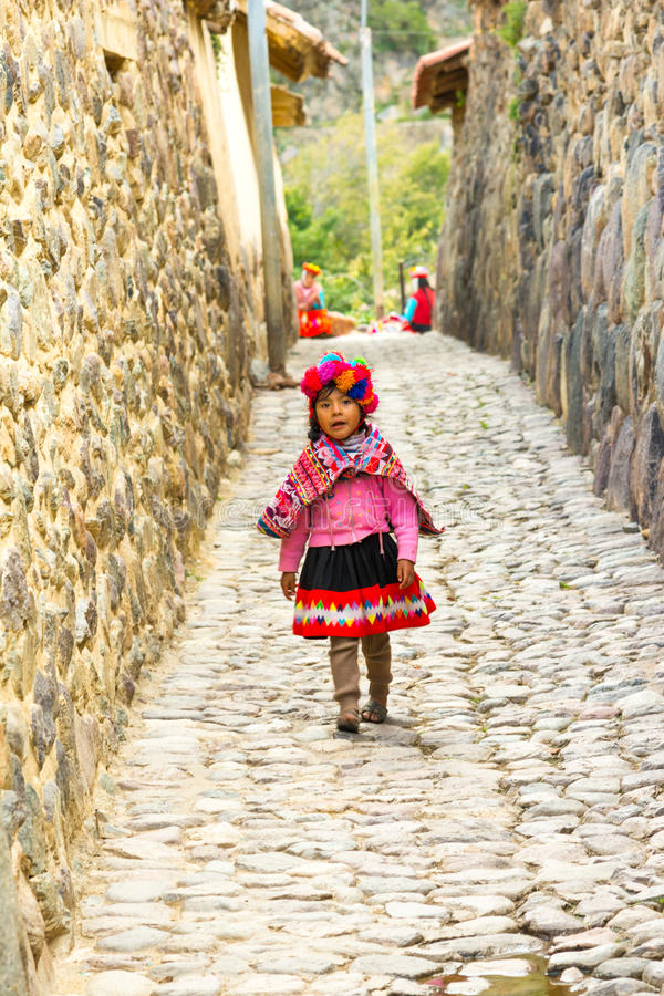 Ollantaytambo, ПЕРУ - 25-ое апреля 2017: Красивая молодая quechua девушка идя на улицы города стоковое фото rf