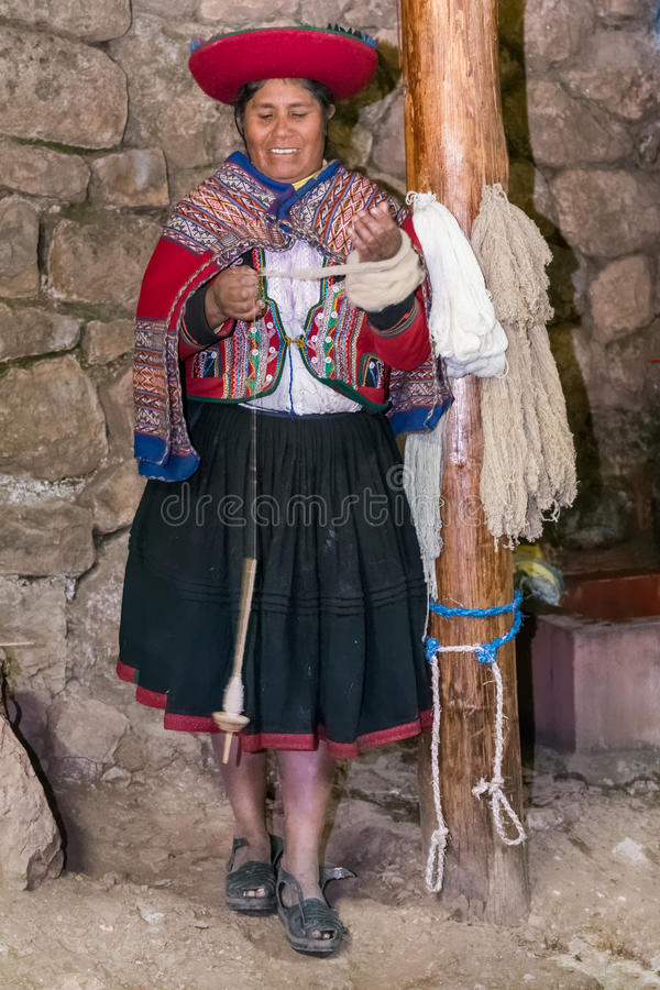 Ollantaytambo, Перу - около июнь 2015: Женщина в традиционных перуанских одеждах делает пряжу от шерстей около Cusco, pe альпаки  стоковая фотография rf