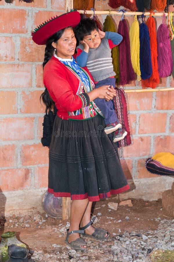 Ollantaytambo, Перу - около июнь 2015: Женщины в традиционных перуанских одеждах держат мальчика около Cusco, Перу стоковая фотография rf