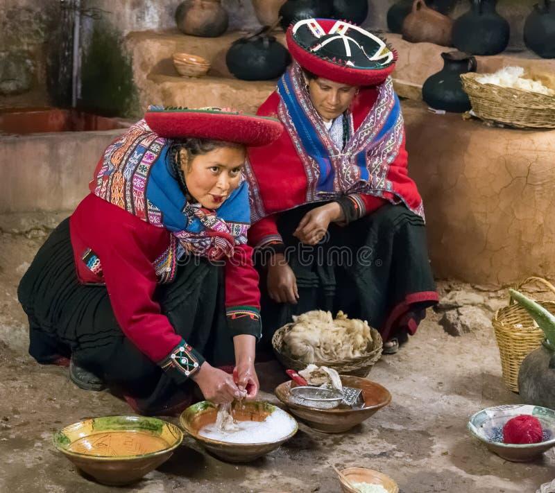 Ollantaytambo, Перу - около июнь 2015: Женщины в традиционных перуанских одеждах используют естественные краски для шерстей альпа стоковые изображения