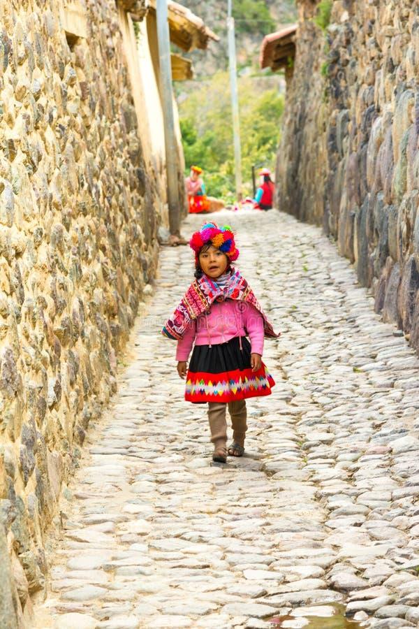 Ollantaytambo PERU - 25 APRIL 2017: Härlig ung quechua flicka som går på gatorna av staden royaltyfri foto