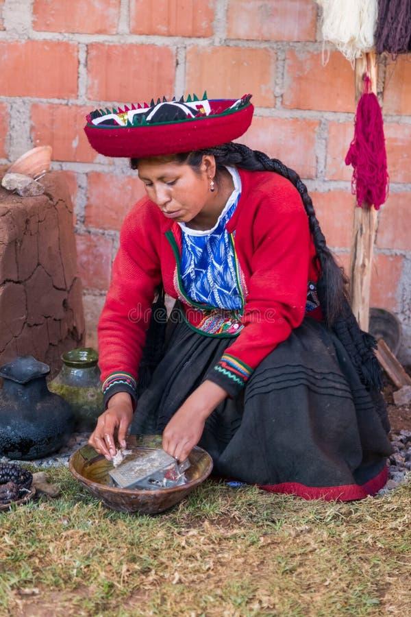 Ollantaytambo, Peru - około Czerwiec 2015: Kobieta w tradycyjny Peruwiańskim odziewa uses naturalnego barwidło dla alpagi i lamy  obraz royalty free
