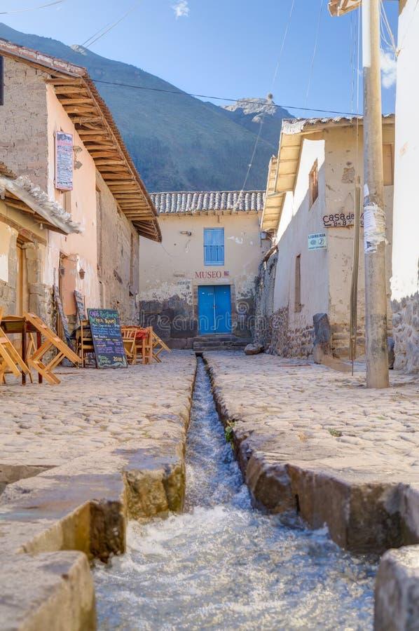Ollantaytambo, Urubamba/Peru - circa Juni 2015: Museum en stroom bij de straat van de stad van Ollantaytambo Inca, Peru stock afbeelding
