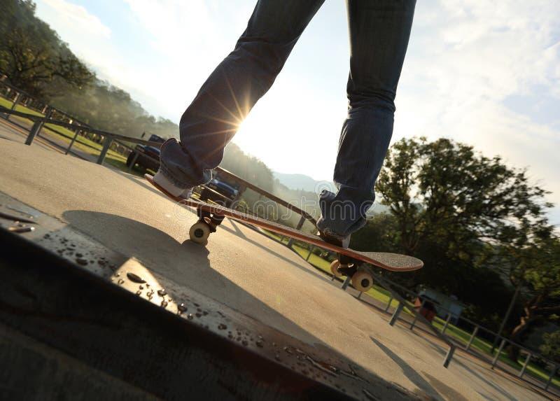 Ollie de pratique en matière de jambes de planchiste à la rampe de skatepark images libres de droits