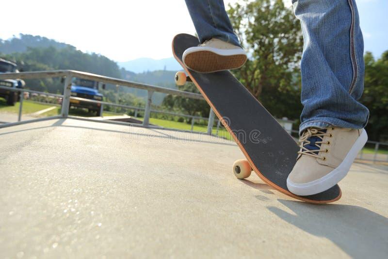 Ollie de pratique en matière de jambes de planchiste à la rampe de skatepark photo libre de droits