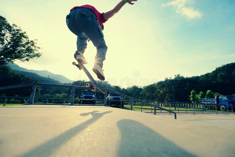 Ollie de pratique en matière de jambes de planchiste à la rampe de skatepark photo stock