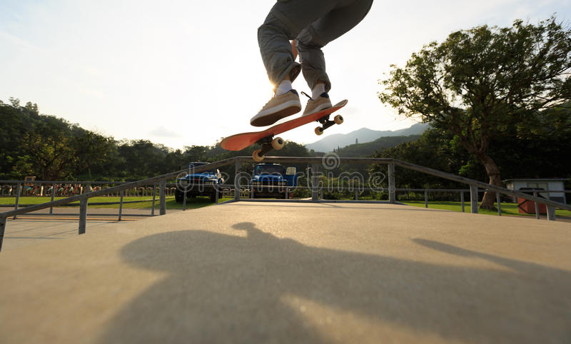 Ollie de pratique en matière de jambes de planchiste à la rampe de skatepark image stock