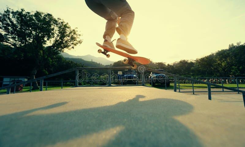 Ollie de pratique en matière de jambes de planchiste à la rampe de skatepark images stock