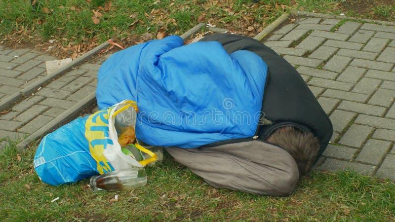 OLOMOUC, REPÚBLICA CHECA, O 2 DE JANEIRO DE 2019: Adormecido superior e sono do homem autêntico dos sem abrigo da emoção no saco- fotos de stock