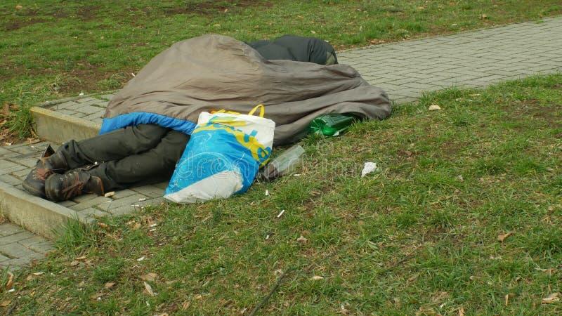 OLOMOUC, REPÚBLICA CHECA, O 2 DE JANEIRO DE 2019: Adormecido superior e sono do homem autêntico dos sem abrigo da emoção no saco- fotos de stock royalty free