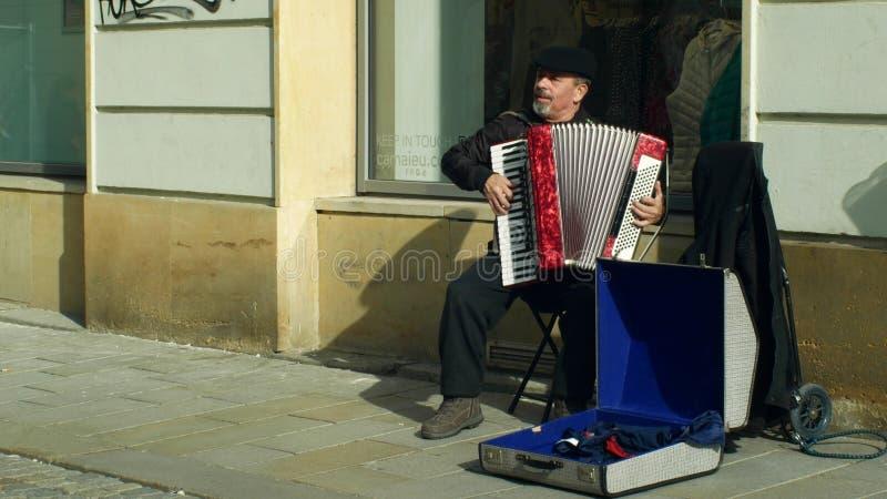 OLOMOUC, REPUBBLICA CECA, IL 29 FEBBRAIO 2019: Uomo zingaresco in città che elemosina soldi in una tazza, musica autentica dei gi fotografia stock libera da diritti
