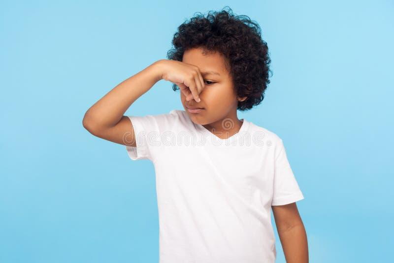 Olor malo Retrato de niño confundido disgustado con la camiseta conteniendo el aliento, pellizcando la nariz fotos de archivo