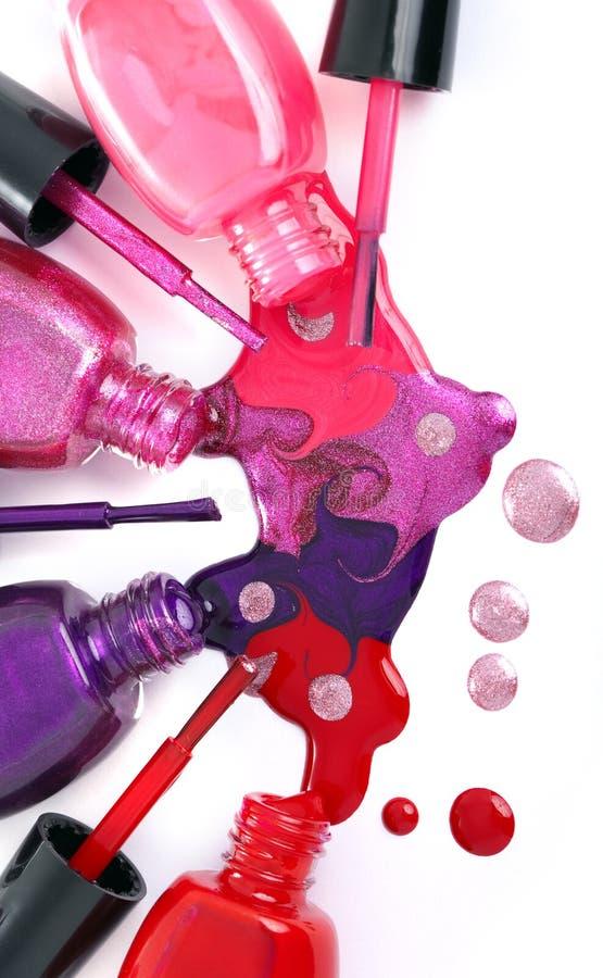 Olored Ð-¡ spikar polermedelfärgstänk som spiller från flaskor arkivfoton