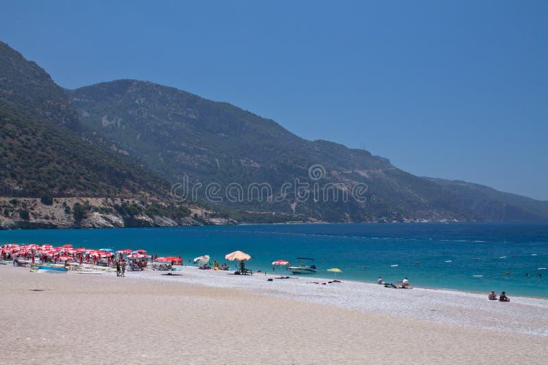 Oludeniz, Турция - 10-ое июля 2012: туристы проводя их летние отпуска наслаждаясь плавать и загорать на чудесном пляже на t стоковая фотография