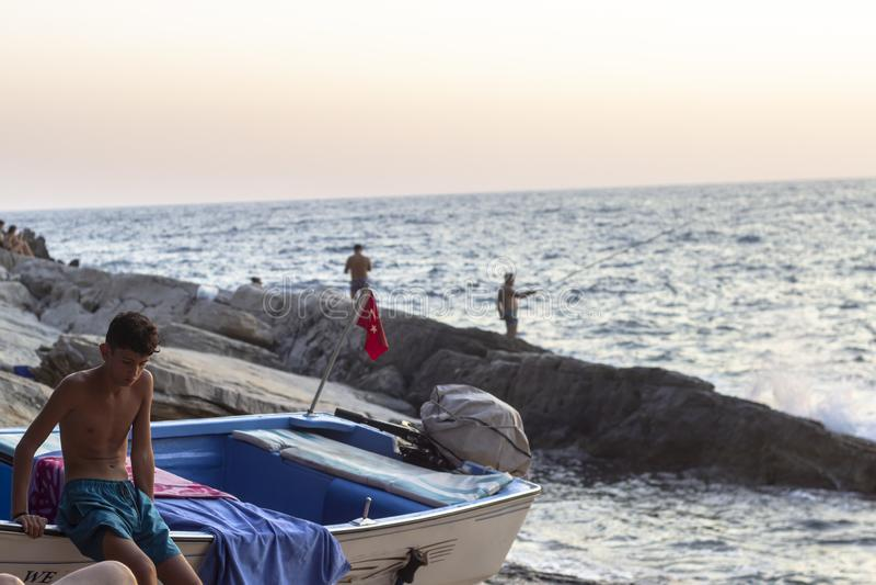 OLUDENIZ - FETHIYE, TURQUIA - 24 DE AGOSTO DE 2018 O tiro limpo de um menino senta-se na vela no tempo do por do sol fotografia de stock royalty free